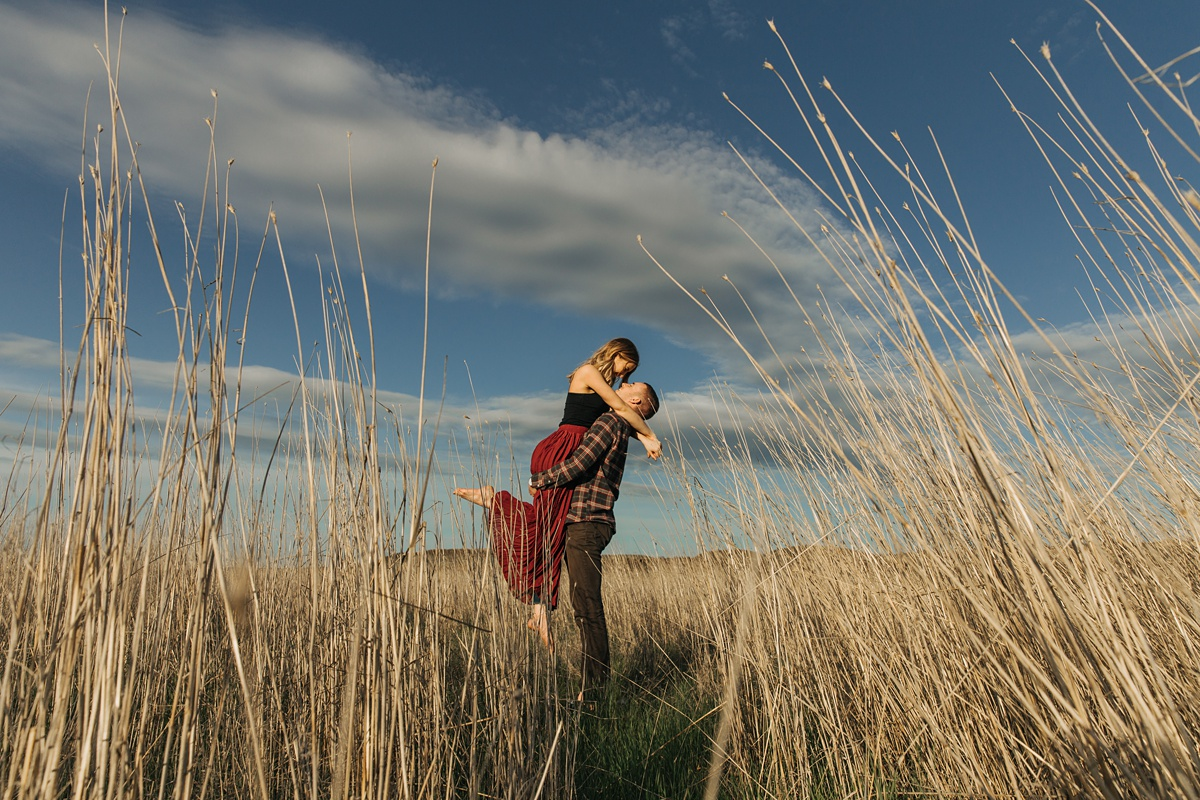 girl being lifted by man in tall grass