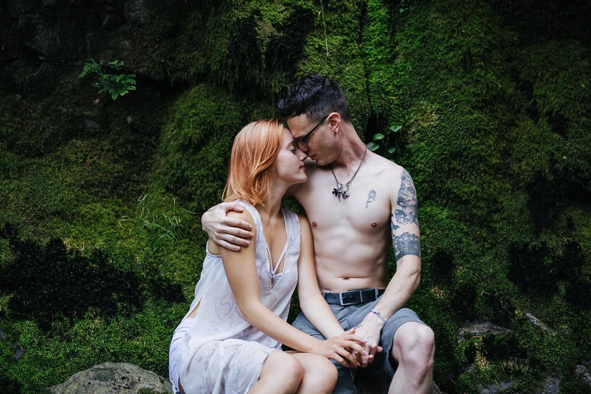 couple sitting on mossy ledge