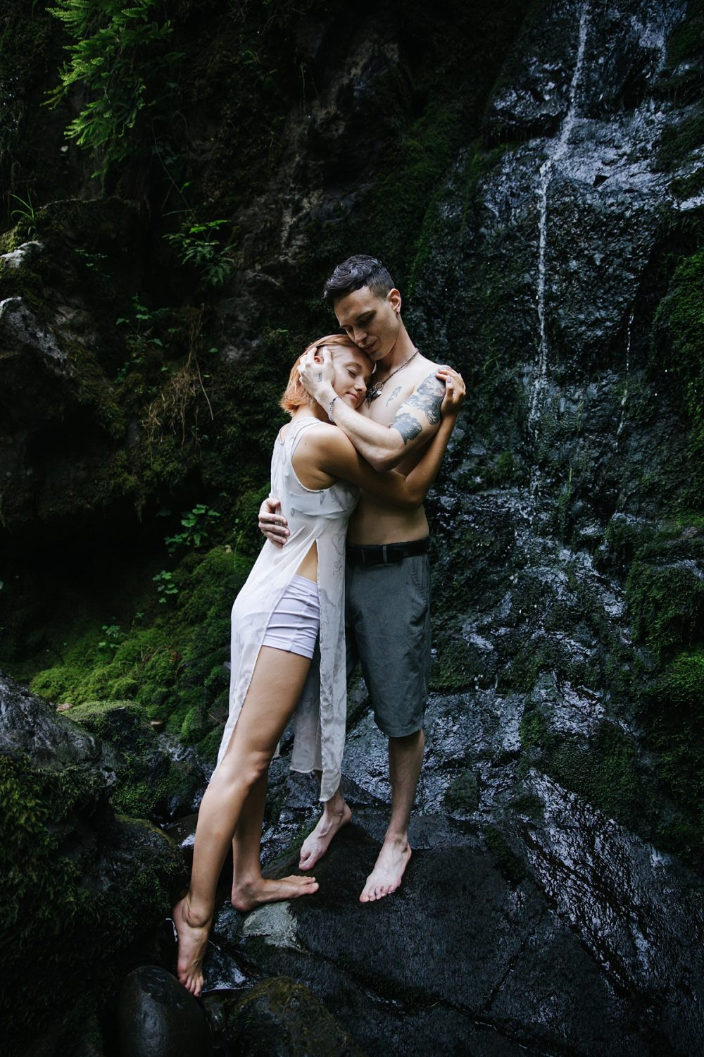 couple standing in waterfall