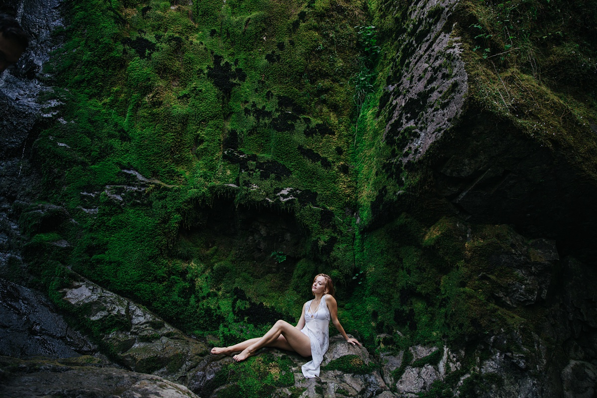 girl sitting on mossy ledge