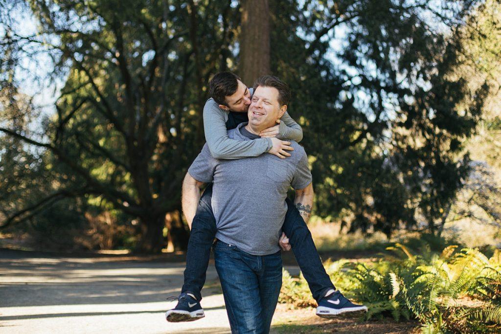 washington park arboretum, gay couple giving each other a piggy back ride