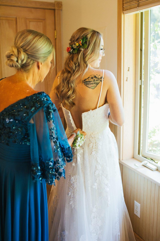 beau lodge wedding bride getting dress zipped by mom