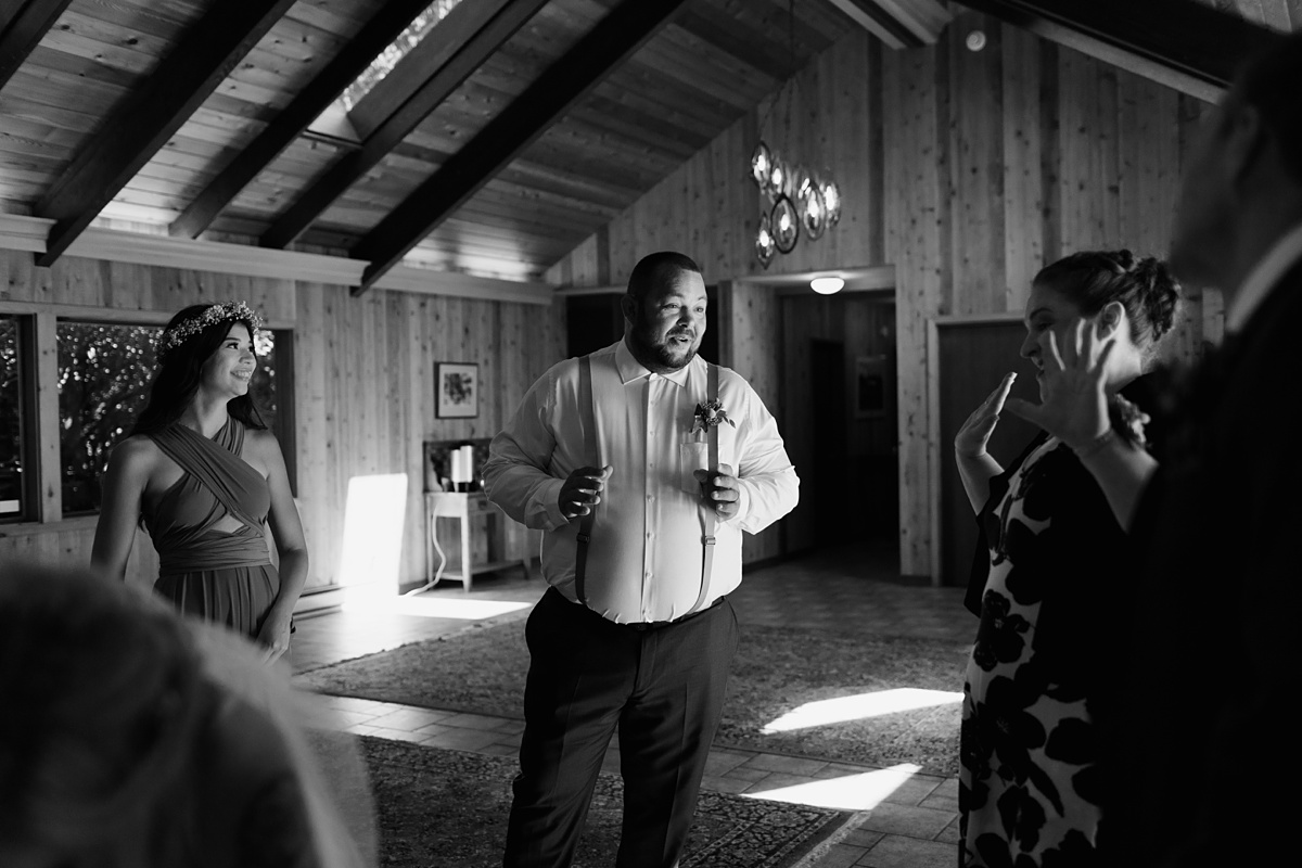 beau lodge wedding black and white portrait of groomsman after wedding while signing license and chatting with family