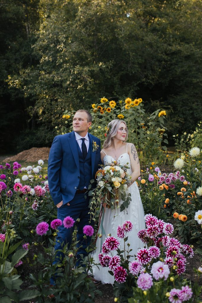 beau lodge wedding bride and groom standing in flower patch