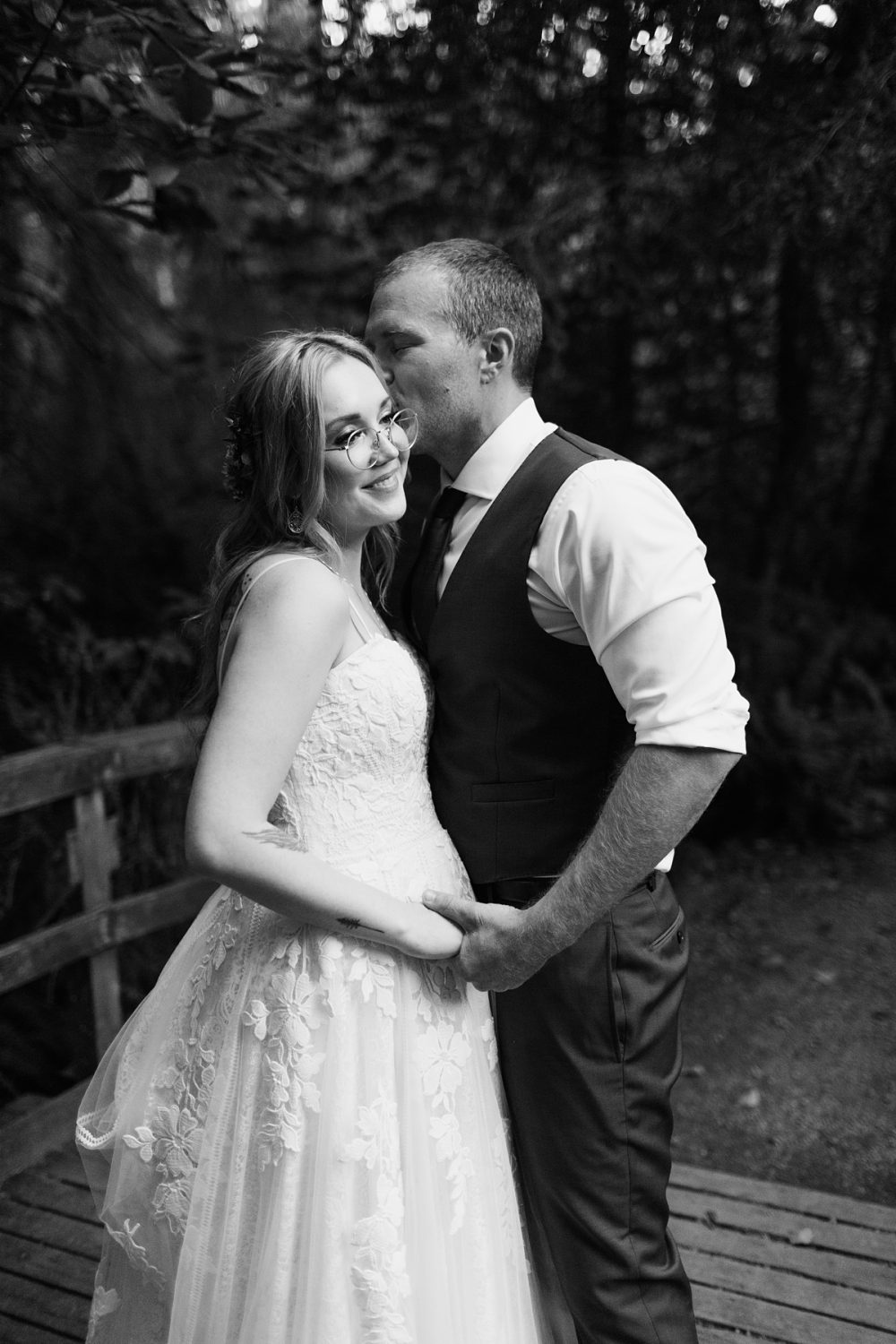 beau lodge wedding bride and groom portraits in forested area with a bridge