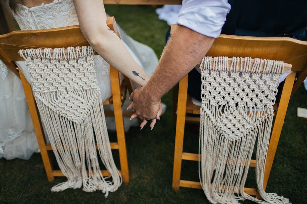 beau lodge wedding bride and groom holding hands while sitting in chairs with handmade macrame backings