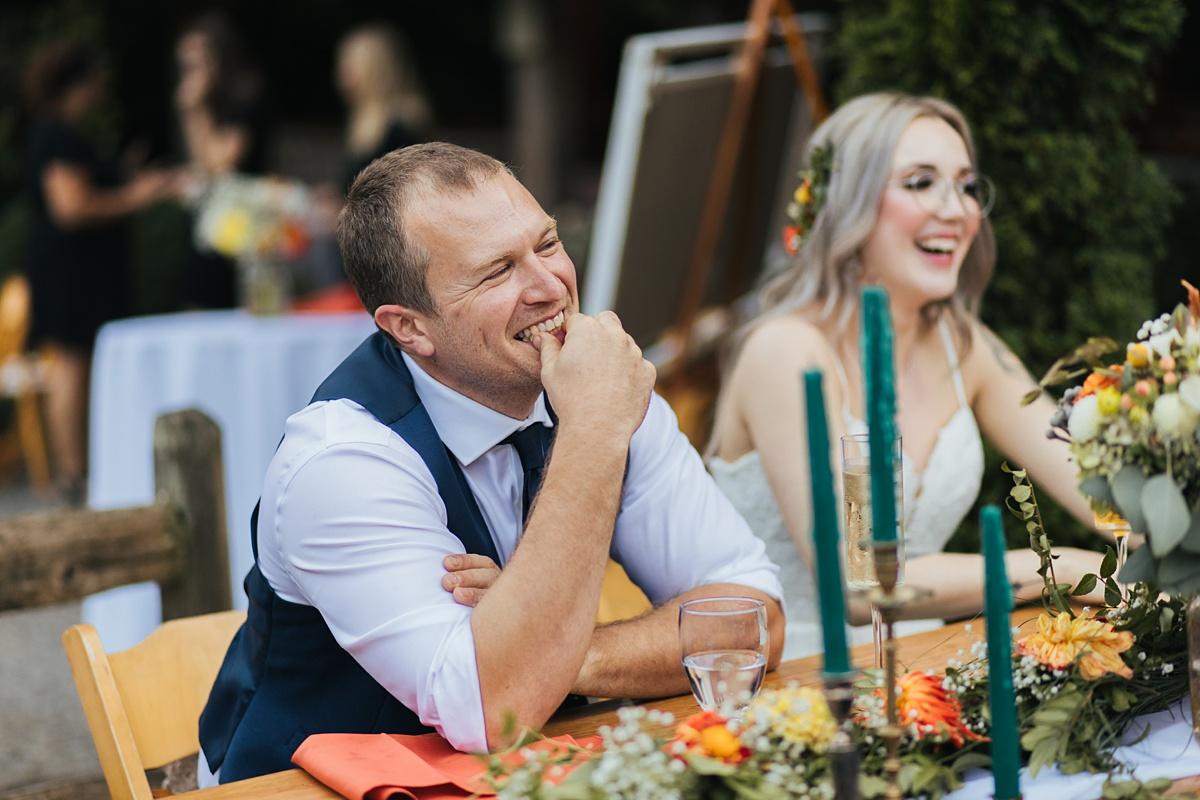 beau lodge wedding smiling groom during toasts