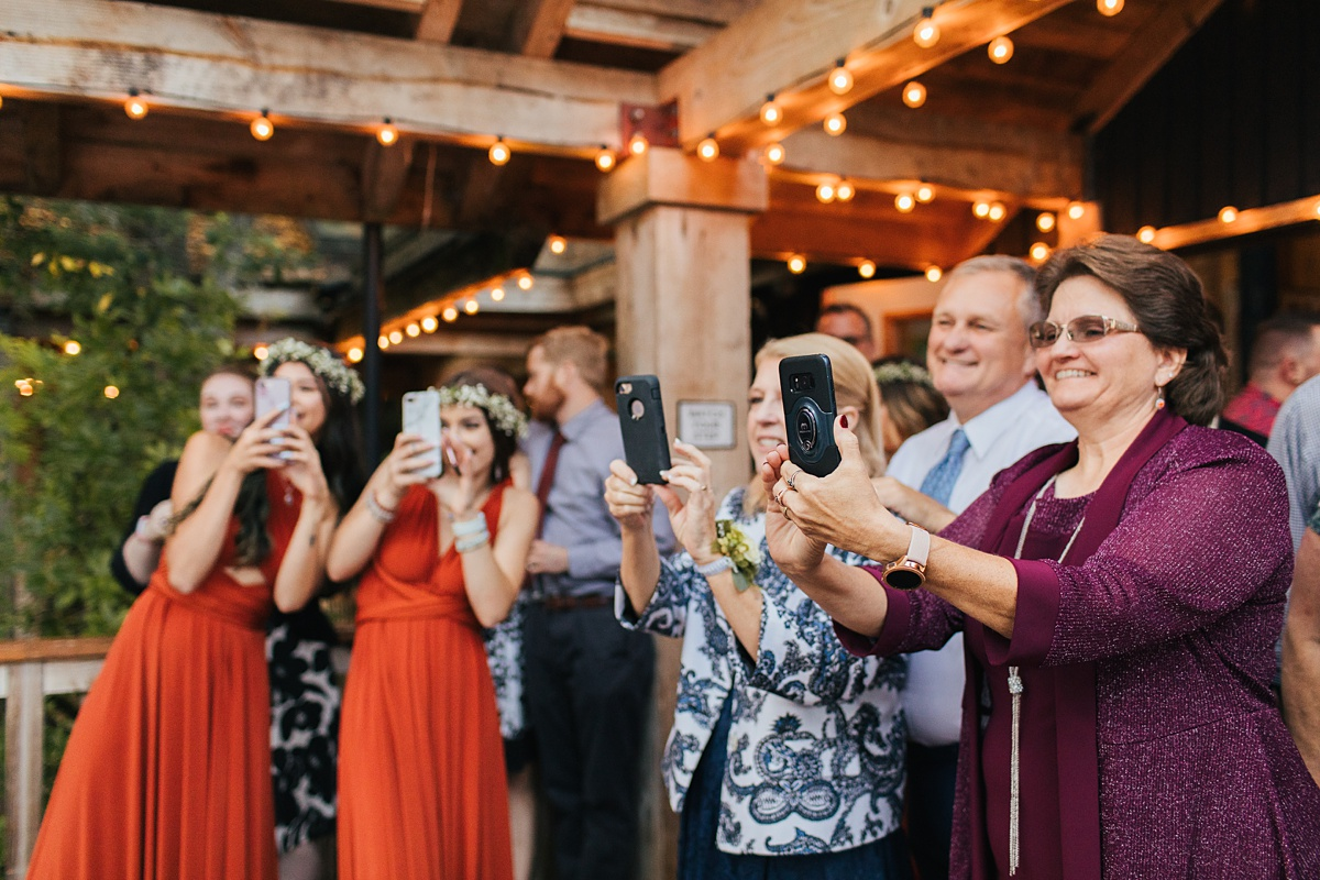 beau lodge wedding family photographing cake cutting with phones