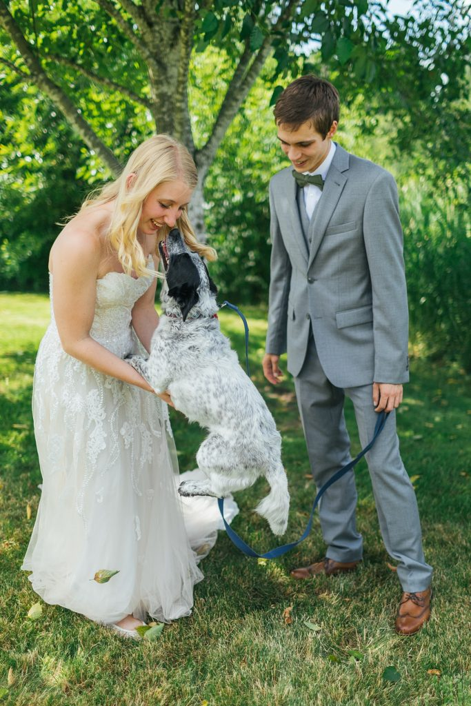 Bostic Lake Ranch Wedding bride and groom posing with their dog who has jumped up and nose booped the bride