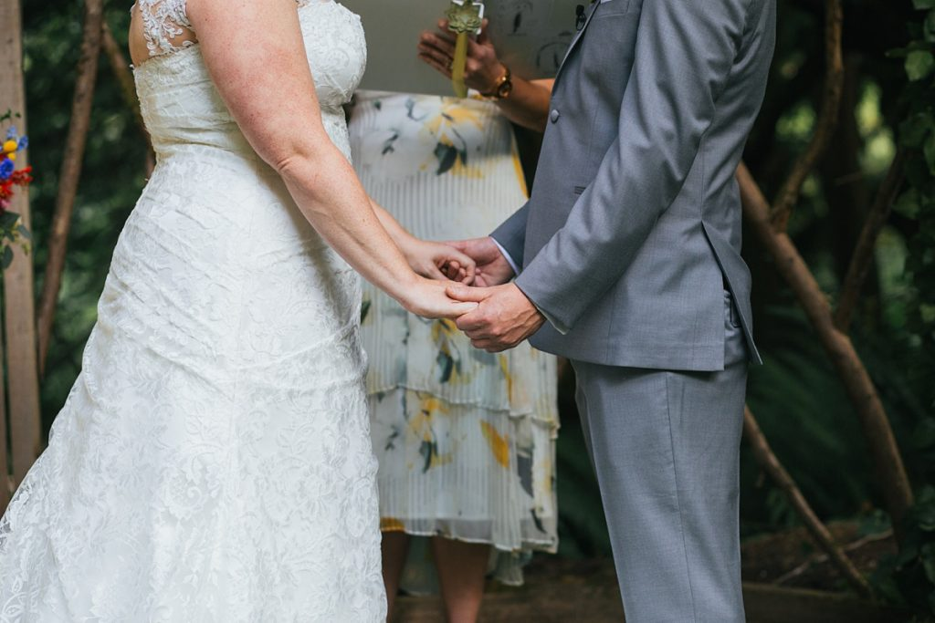 TreeHouse Point Wedding bride and groom holding hands during ceremony