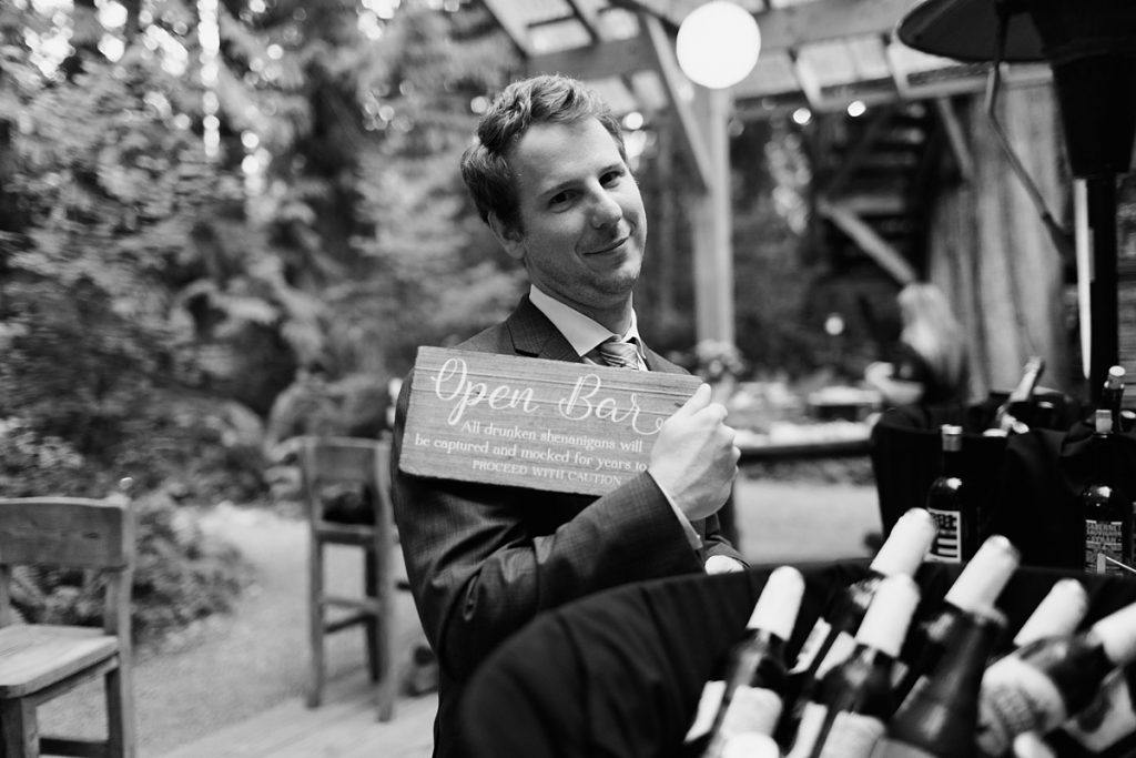 TreeHouse Point Wedding man holding open bar sign