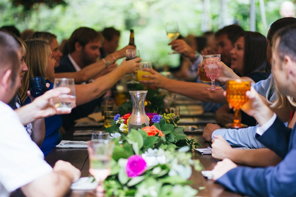 TreeHouse Point Wedding guests toasting and close up of seattle farm table table