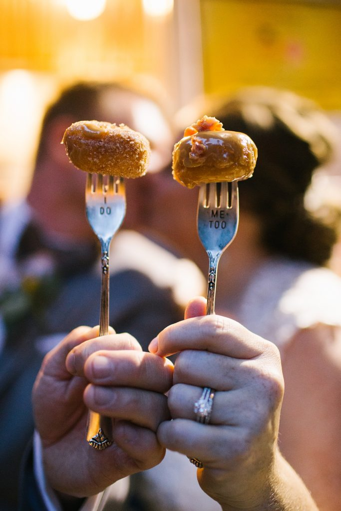"""TreeHouse Point Wedding hot revolution donuts on """"I do"""" """"me too"""" forks with bride and groom kissing in background"""