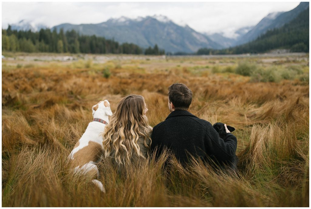 Snoqualmie Pass Lake Keechelus Engagement Session sitting in long grass with dogs looking at mountains