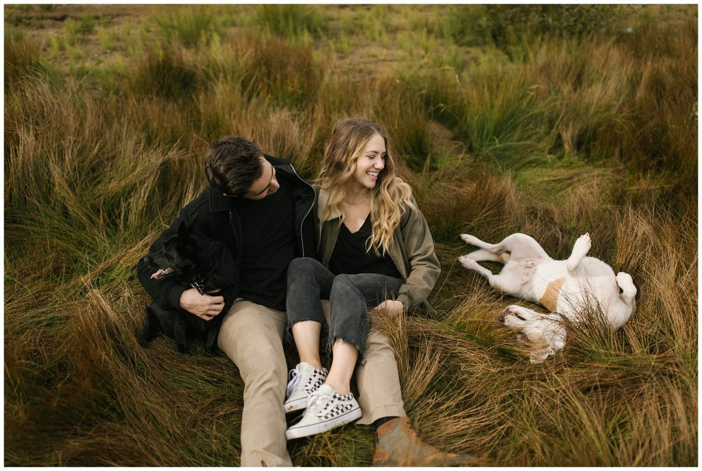 Snoqualmie Pass Lake Keechelus Engagement Session sitting in long grass with dogs, one dog rolling over
