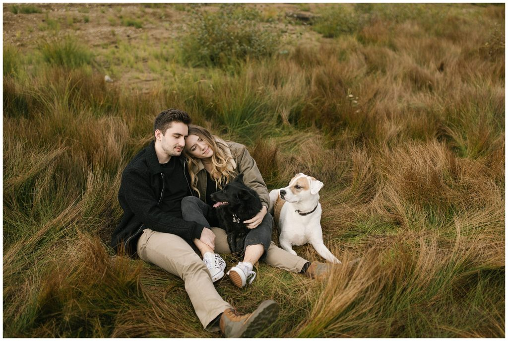 Snoqualmie Pass Lake Keechelus Engagement Session sitting in long grass with dogs