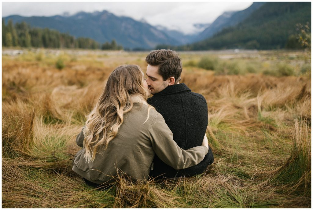Snoqualmie Pass Lake Keechelus Engagement Session sitting in long grass, kissing with mountains in the background