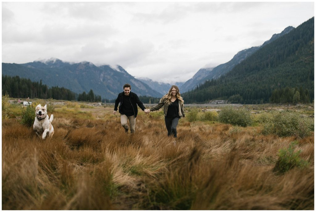 Snoqualmie Pass Lake Keechelus Engagement Session running through long grass holding hands
