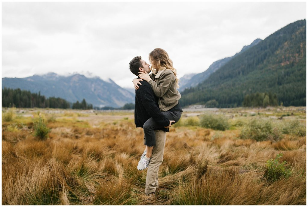 Snoqualmie Pass Lake Keechelus Engagement Session boy picking girl up koala bear style