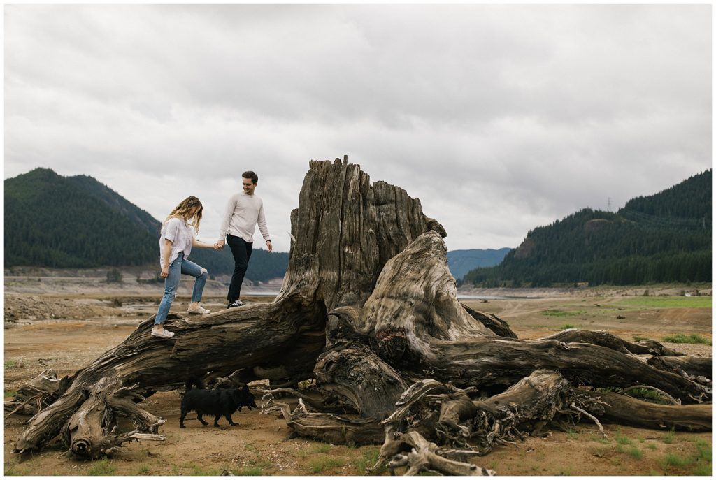 Snoqualmie Pass Lake Keechelus Engagement Session climbing on large tree stump