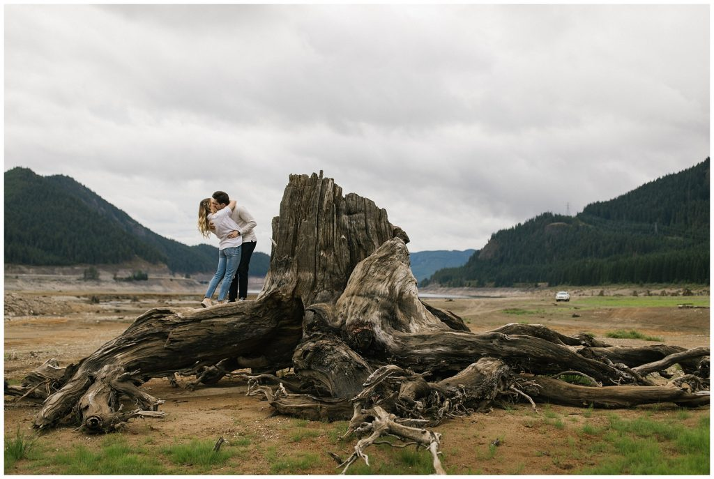 Snoqualmie Pass Lake Keechelus Engagement Session kissing while standing on top of large tree stump
