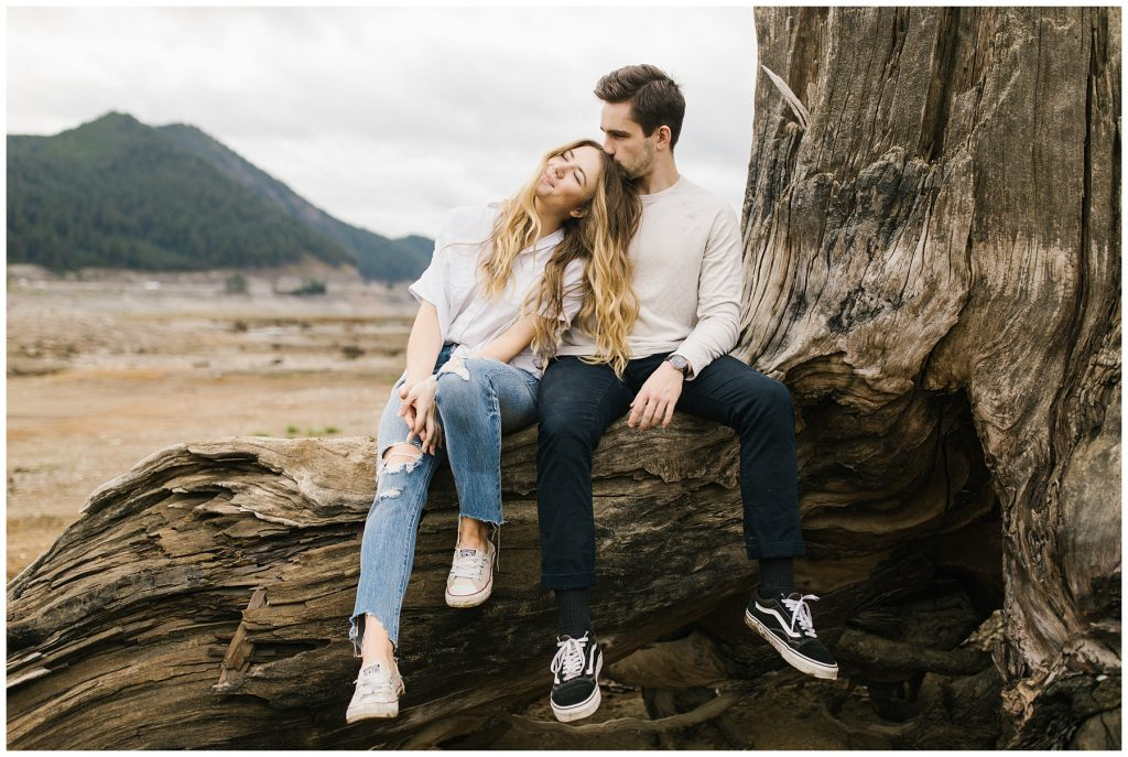 Snoqualmie Pass Lake Keechelus Engagement Session sitting on large tree stump together