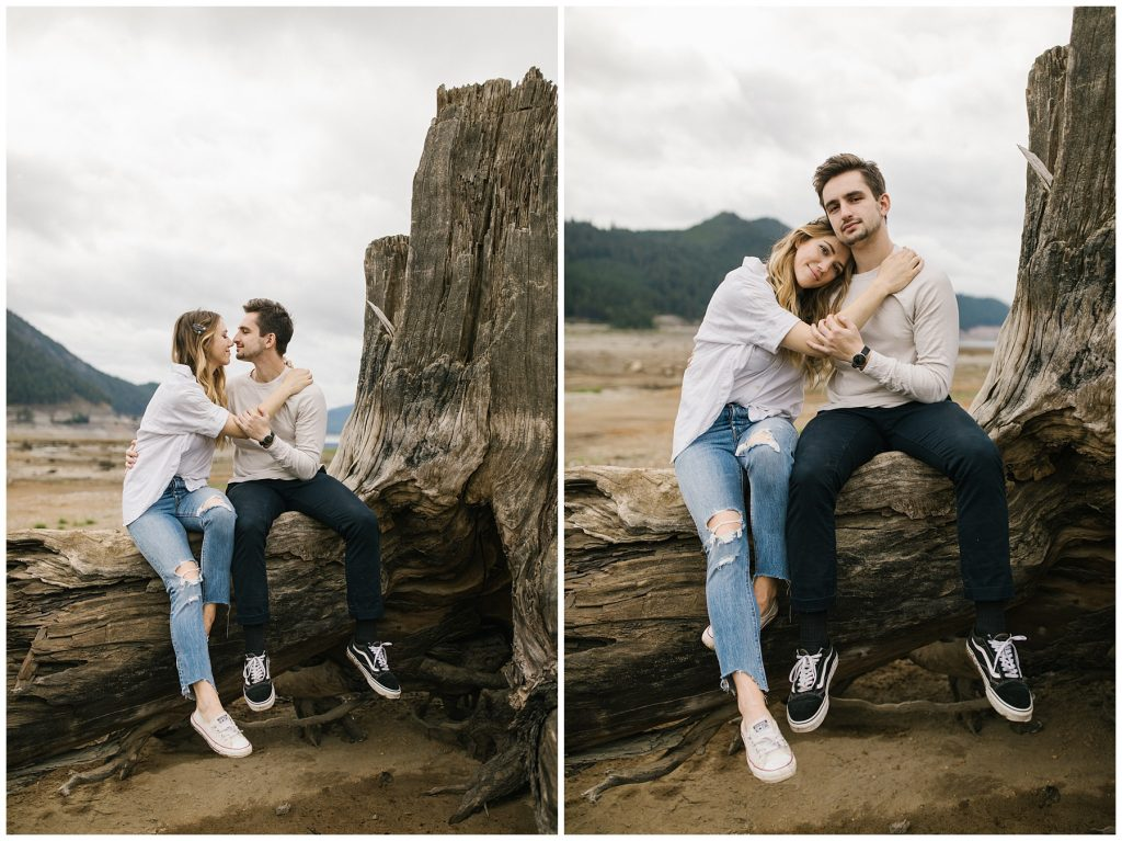 Snoqualmie Pass Lake Keechelus Engagement Session couple sitting on large tree stump together