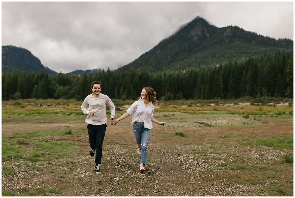 Snoqualmie Pass Lake Keechelus Engagement Session couple running while holding hands