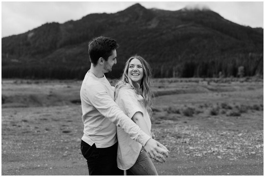 Snoqualmie Pass Lake Keechelus Engagement Session black and white photo of couple  goofy walking together