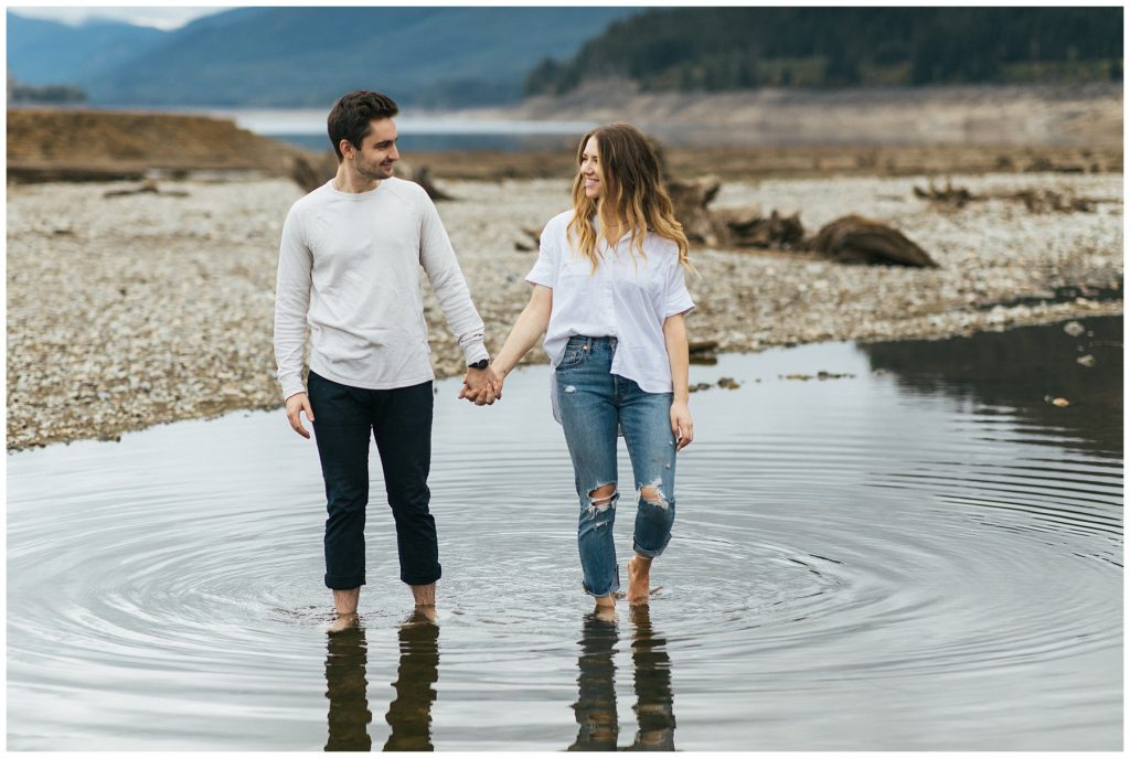 Snoqualmie Pass Lake Keechelus Engagement Session couple walking through large puddle of water
